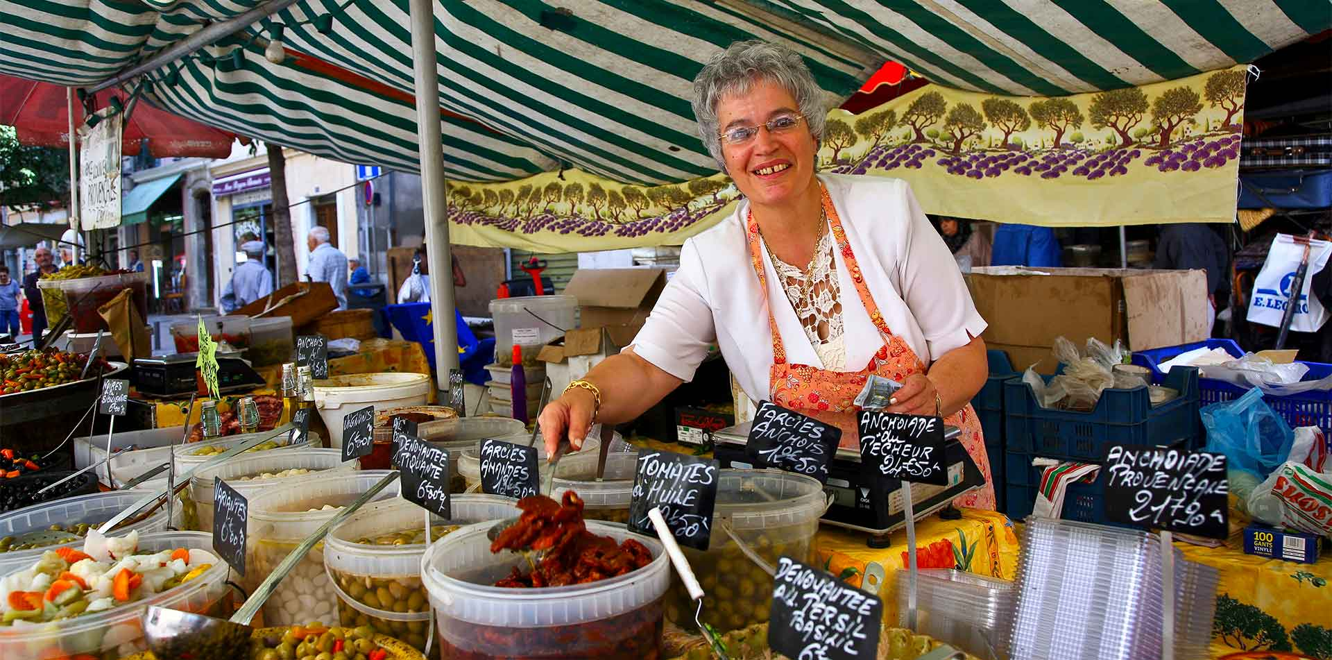 Europe France Provence French woman in market selling food olives and sun-dried tomatoes - luxury vacation destinations