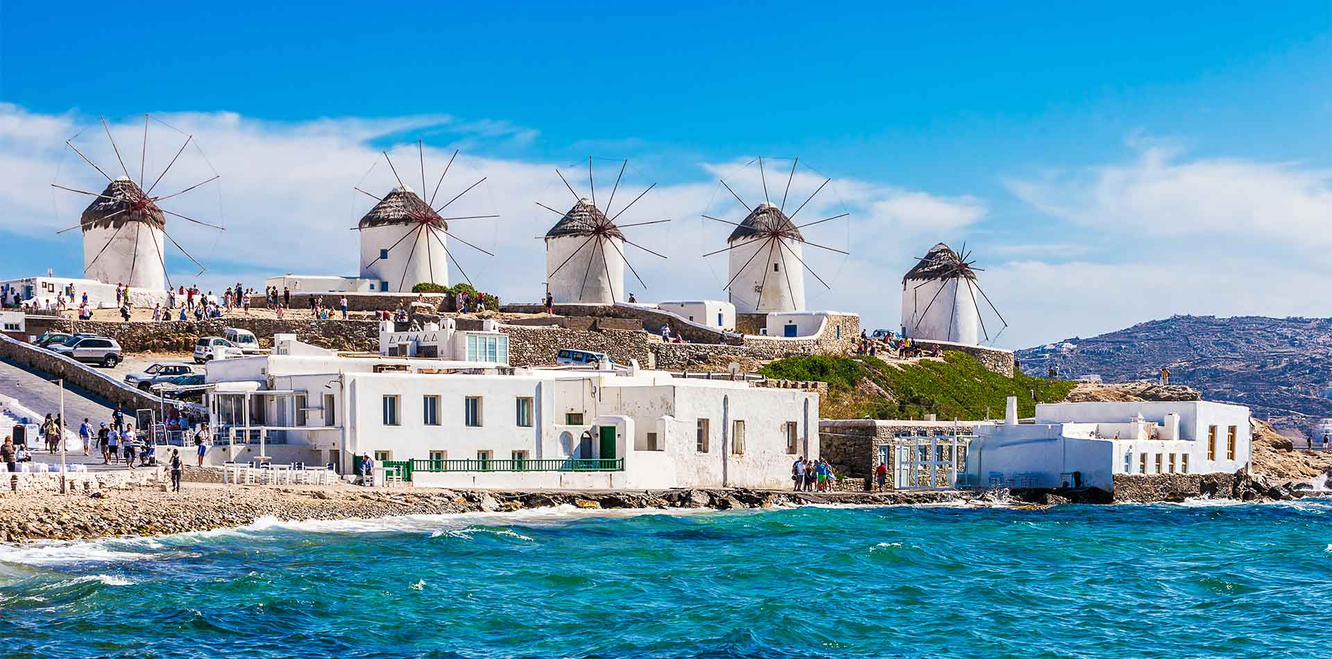 Europe Greece Mykonos Island iconic windmills along coastline with blue water - luxury vacation destinations