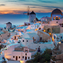 Europe Greece Santorini white buildings on cliffside overlooking ocean at night - luxury vacation destinations