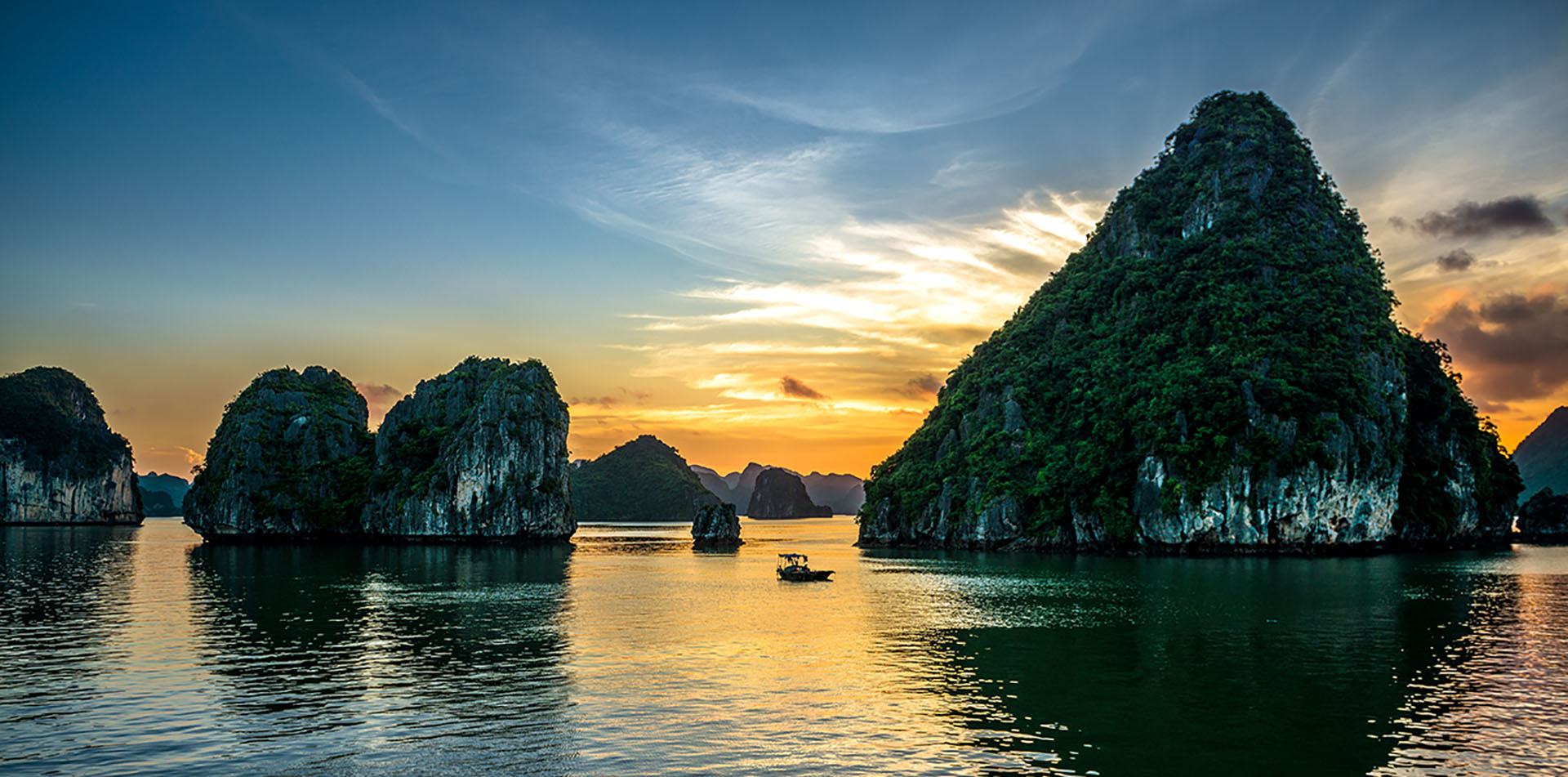 Asia Vietnam sunset over the water and karst formations of Halong Bay - luxury vacation destinations
