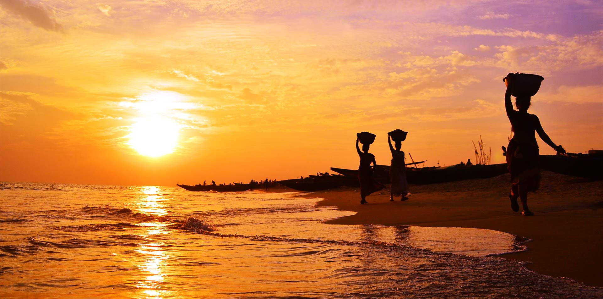 Asia India women carrying baskets along the shoreline at sunset - luxury vacation destinations