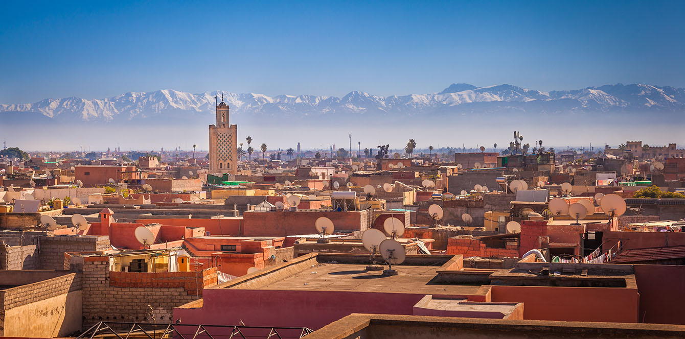 Africa Morocco Marrakesh beautiful snow-capped Atlas Mountains and crowded city view - luxury vacation destinations