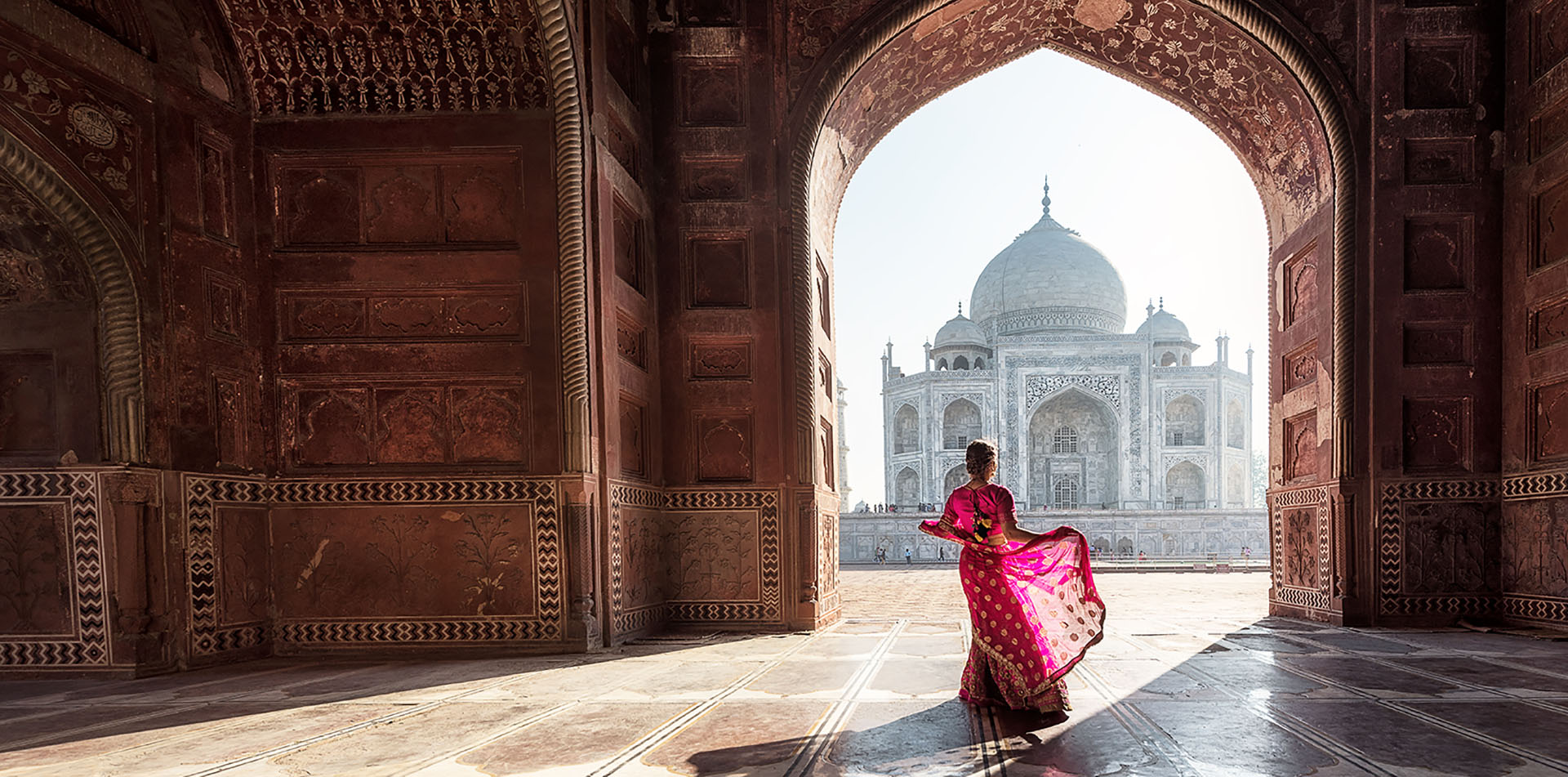 Asia India woman in sari dancing under an archway at Taj Mahal UNESCO world heritage site - luxury vacation destinations