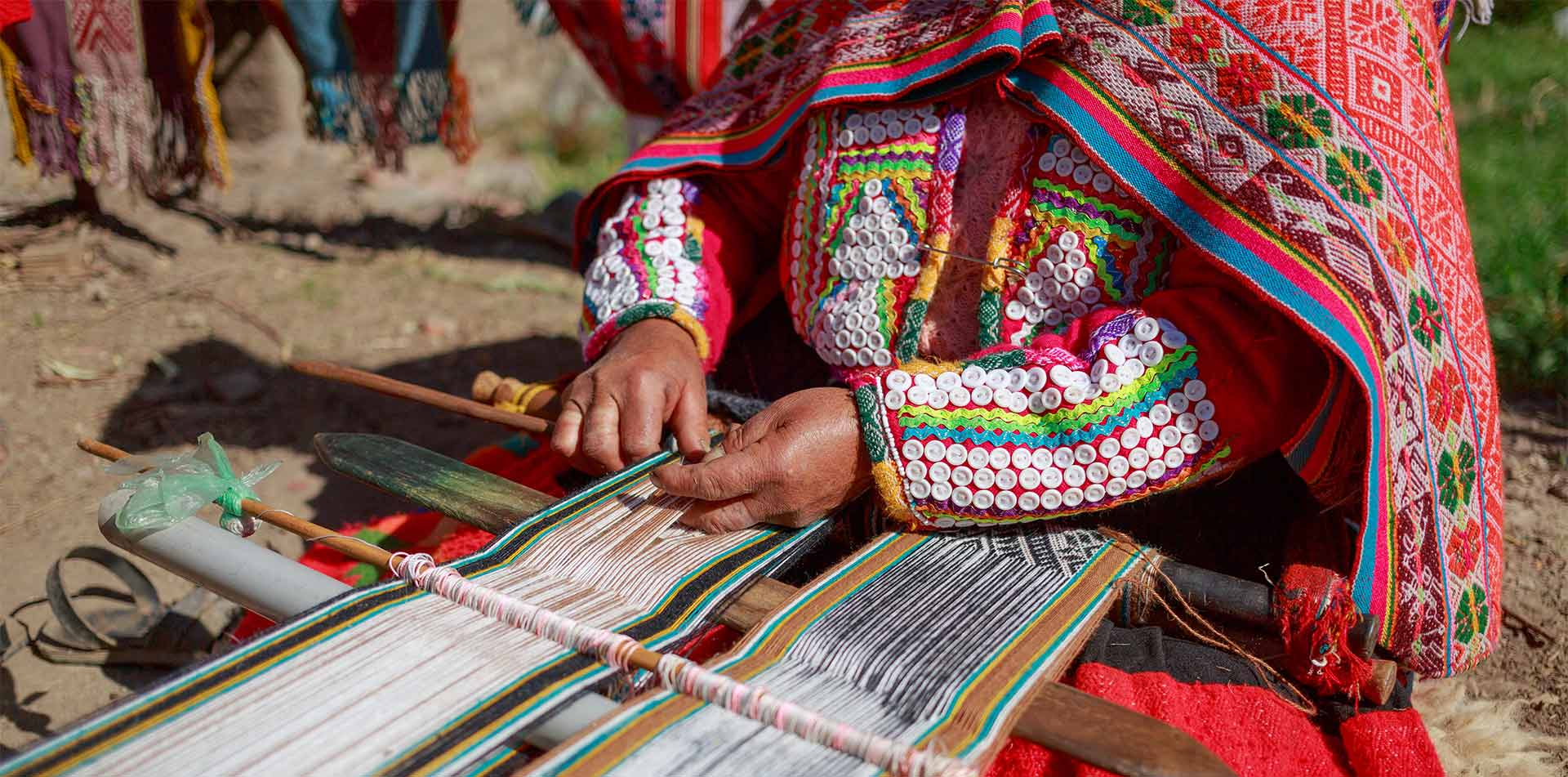 South America Peru Huilloc Sacred Valley traditional Quechua woman weaving colorful thread - luxury vacation destinations