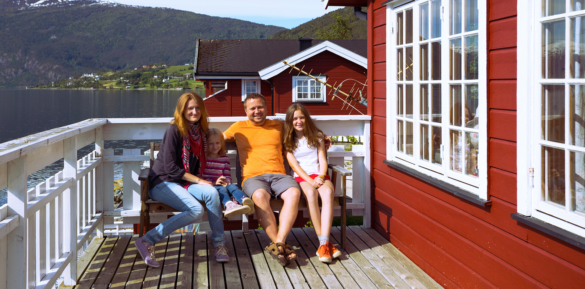 Europe Norway family sitting on bench at Reine Rorbuer by Classic Norway Hotels - luxury vacation destinations