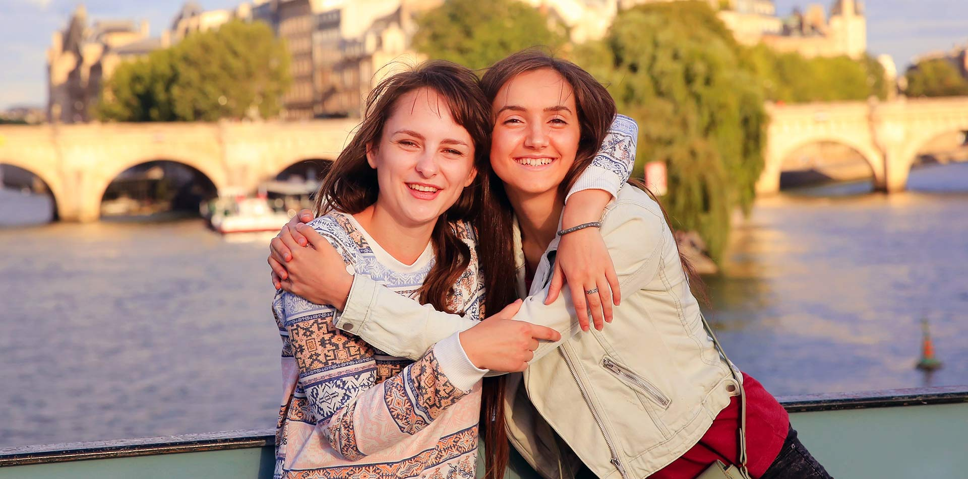 Europe France Paris young girls smiling and hugging with the Siene River in background - luxury vacation destinations