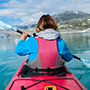 Woman kayaking on Styggvatnet Glacier Lake, Norway