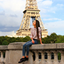 Europe France Paris young girl smiling and posing with historic Eiffel Tower in background - luxury vacation destinations