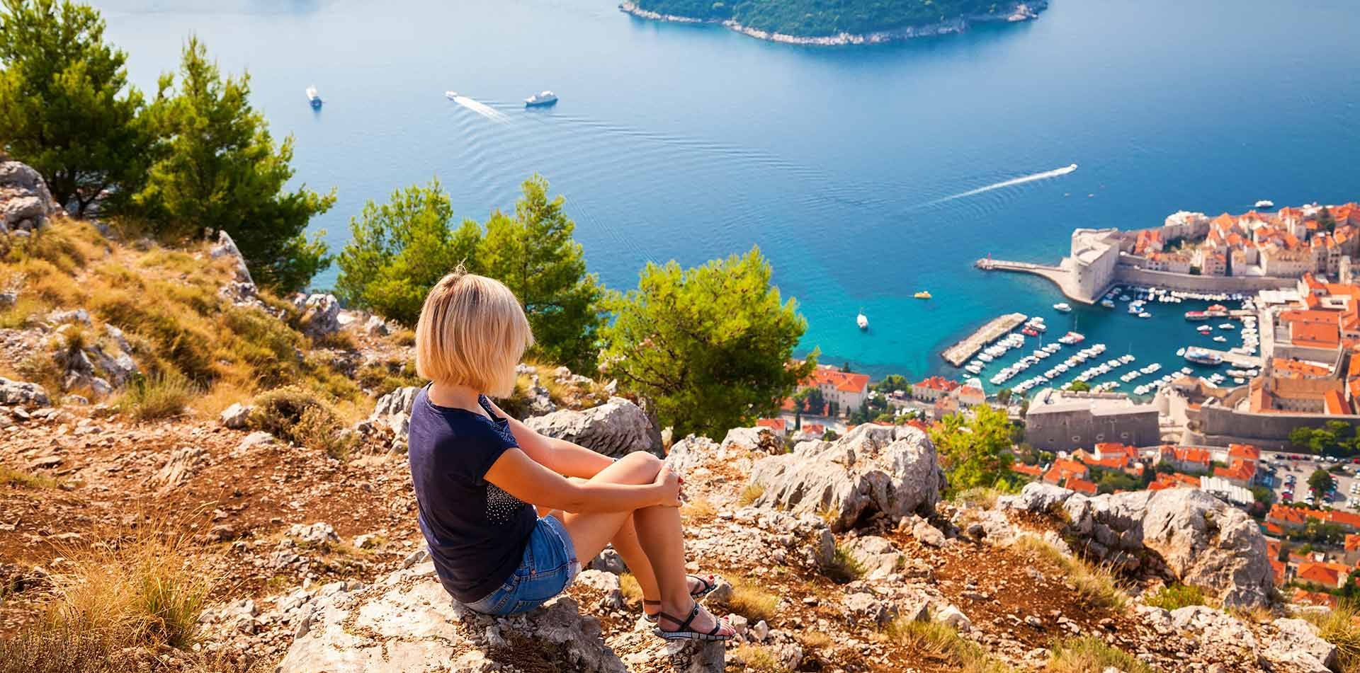 Europe Croatia Dalmatian Coast Dubrovnik young woman looking rocky terrain scenic harbor - luxury vacation destinations