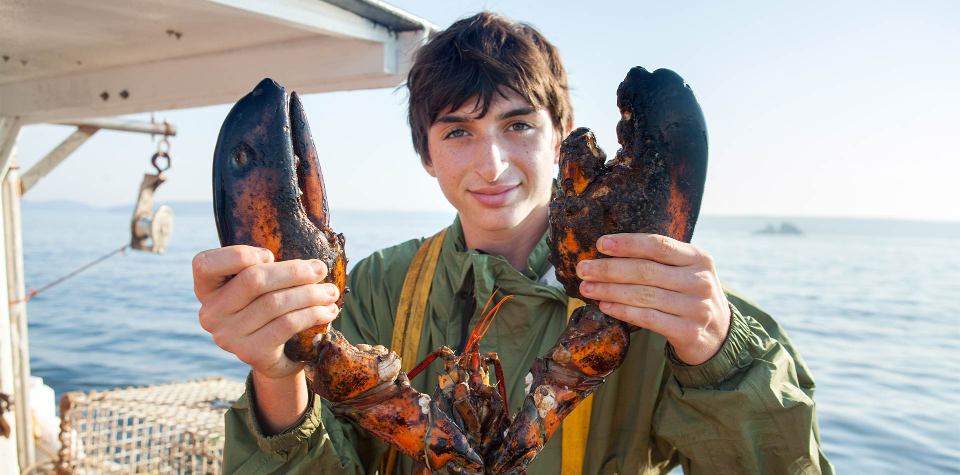 North America Canada Nova Scotia young man holding large lobster fishing boat blue water - luxury vacation destinations