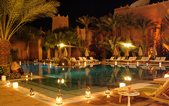 Africa Morocco Ouarzazate Berbere Palace beautiful outdoor pool at night bright lanterns  - luxury vacation destinations