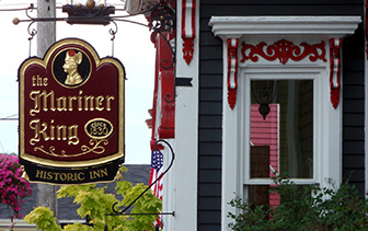 North America Canada Nova Scotia Lunenberg Mariner King Inn historic grey Victorian red sign - luxury vacation destinations
