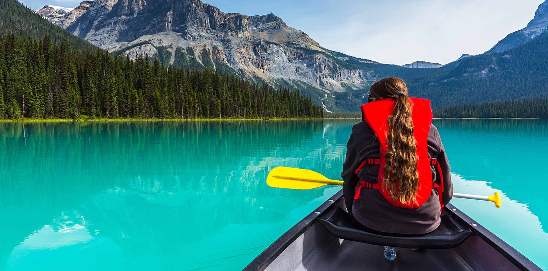 North America Canada British Columbia Yoho Rockies mountain Emerald Lake canoe blue water girl - luxury vacation destinations
