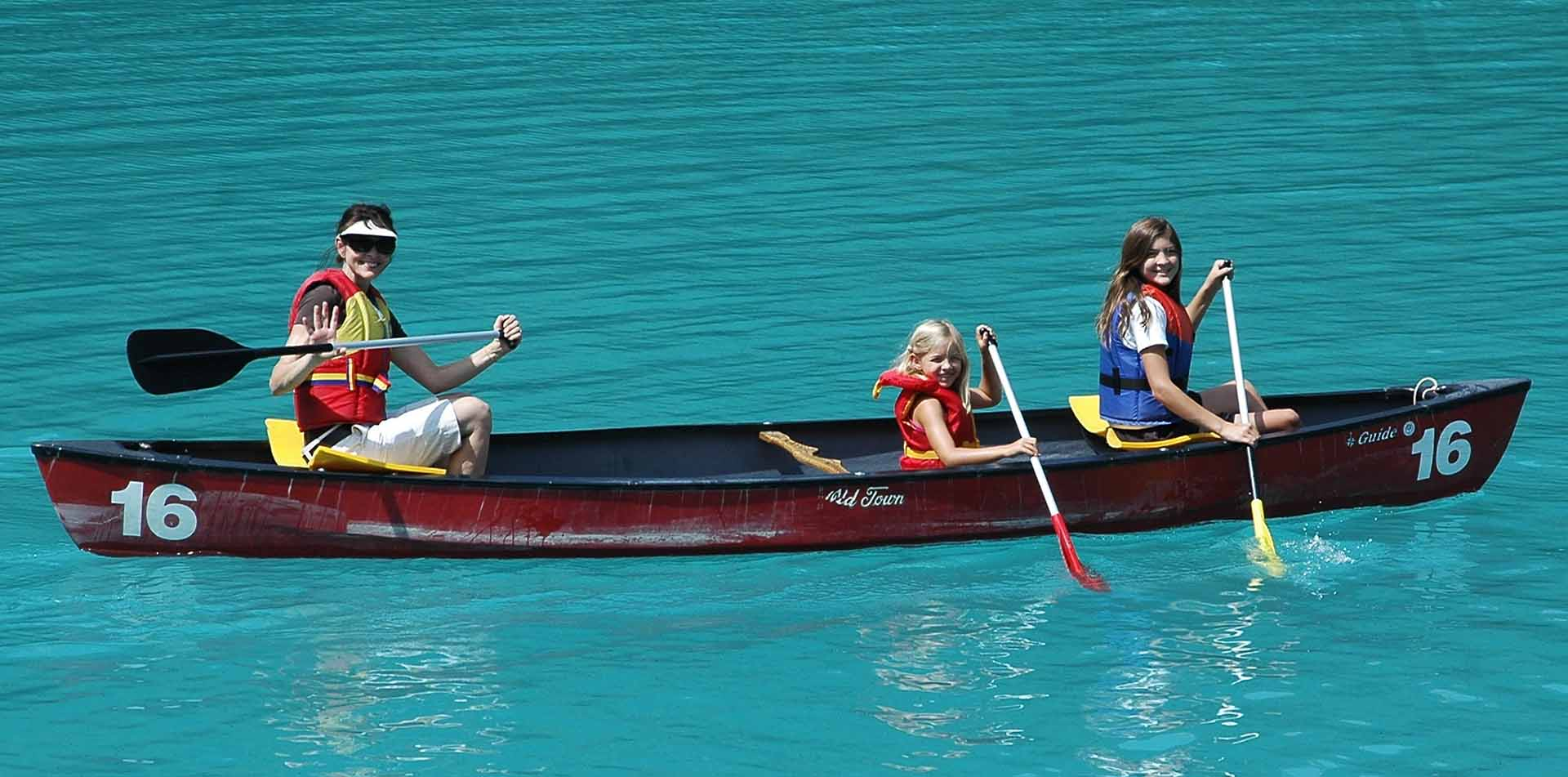 North America Canada British Columbia Rockies Emerald Lake canoe blue water family smile - luxury vacation destinations