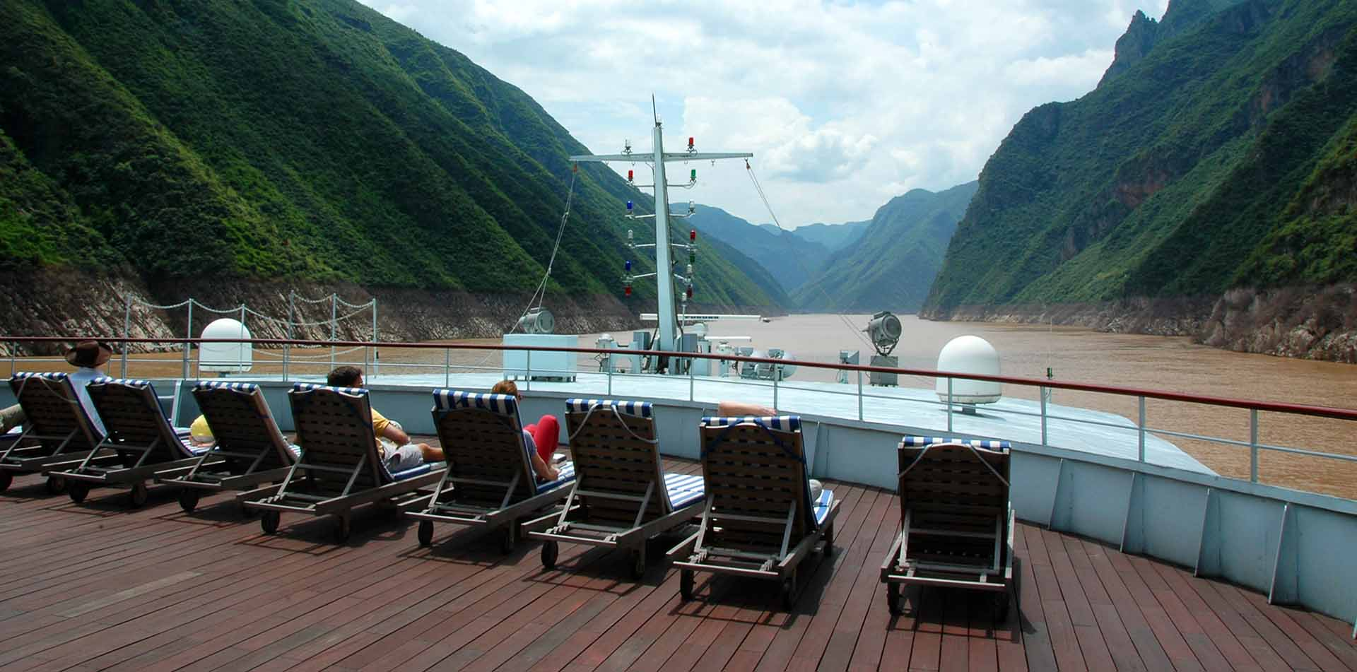 Asia China people lounging in chairs on the bow of a Yangtze River cruise ship - luxury vacation destinations