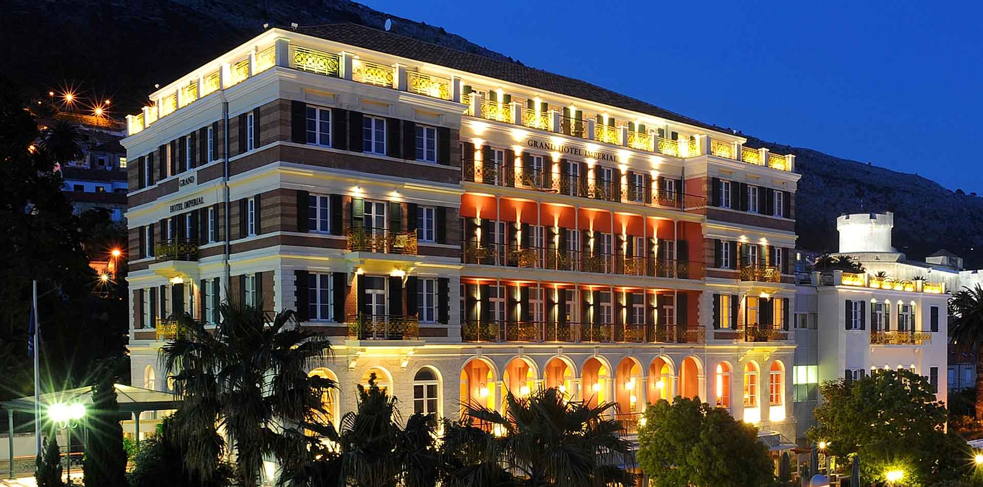 Europe Croatia Hilton Imperial Dubrovnik Hotel elegant exterior lights night palm trees - luxury vacation destinations