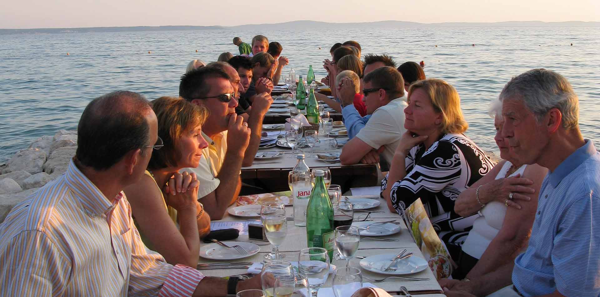 Europe Croatia Dalmatian Coast group eating dinner beautiful waterfront sunset - luxury vacation destinations