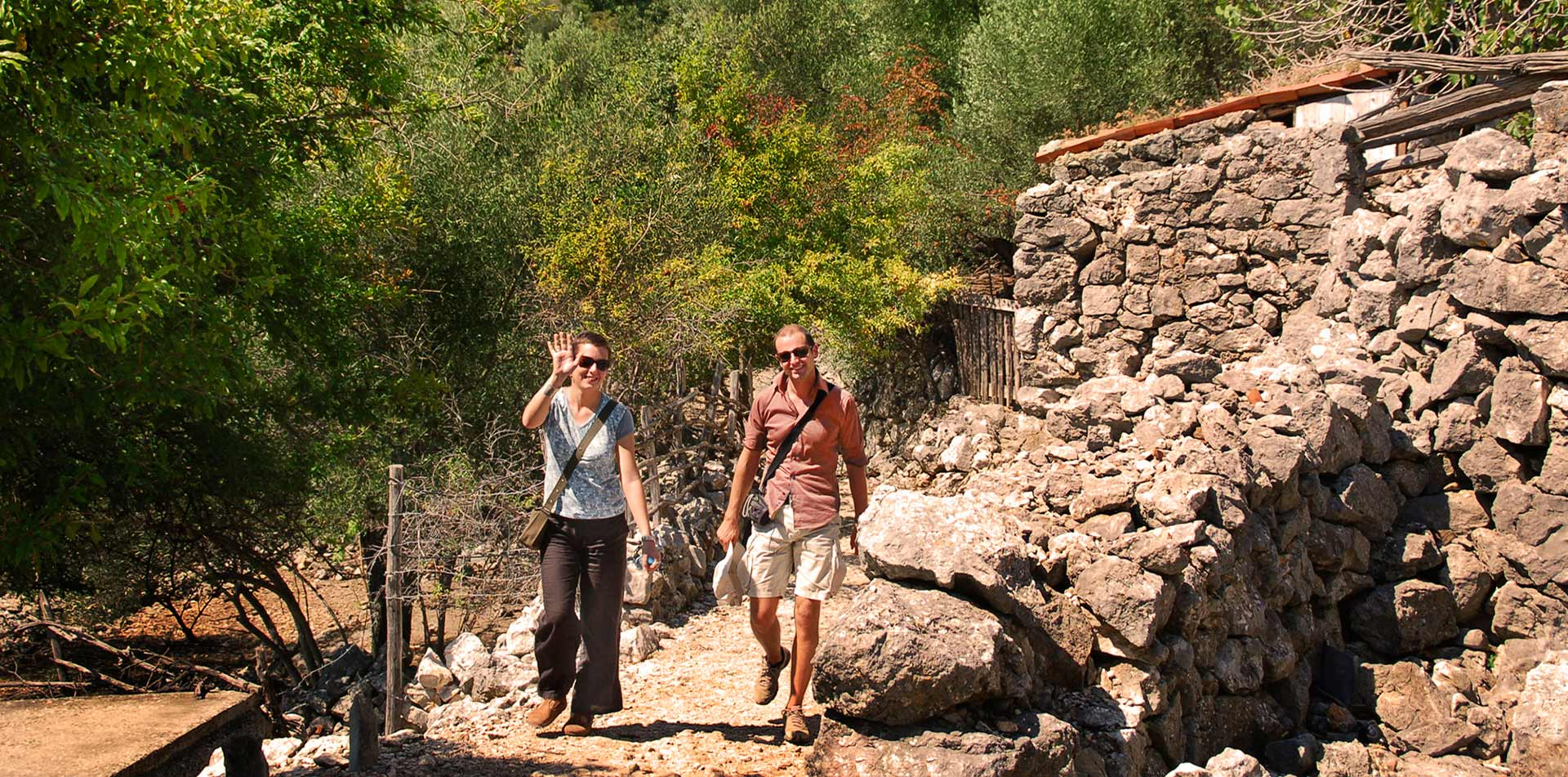 Europe Croatia happy couple walking woman waving scenic green landscape rocky trail hike - luxury vacation destinations