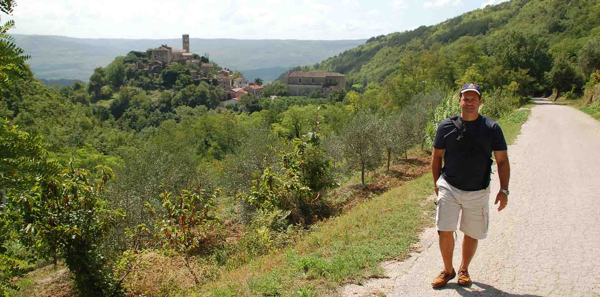Europe Croatia Istria man walking on paved road old historic hiltop town lush landscape - luxury vacation destinations