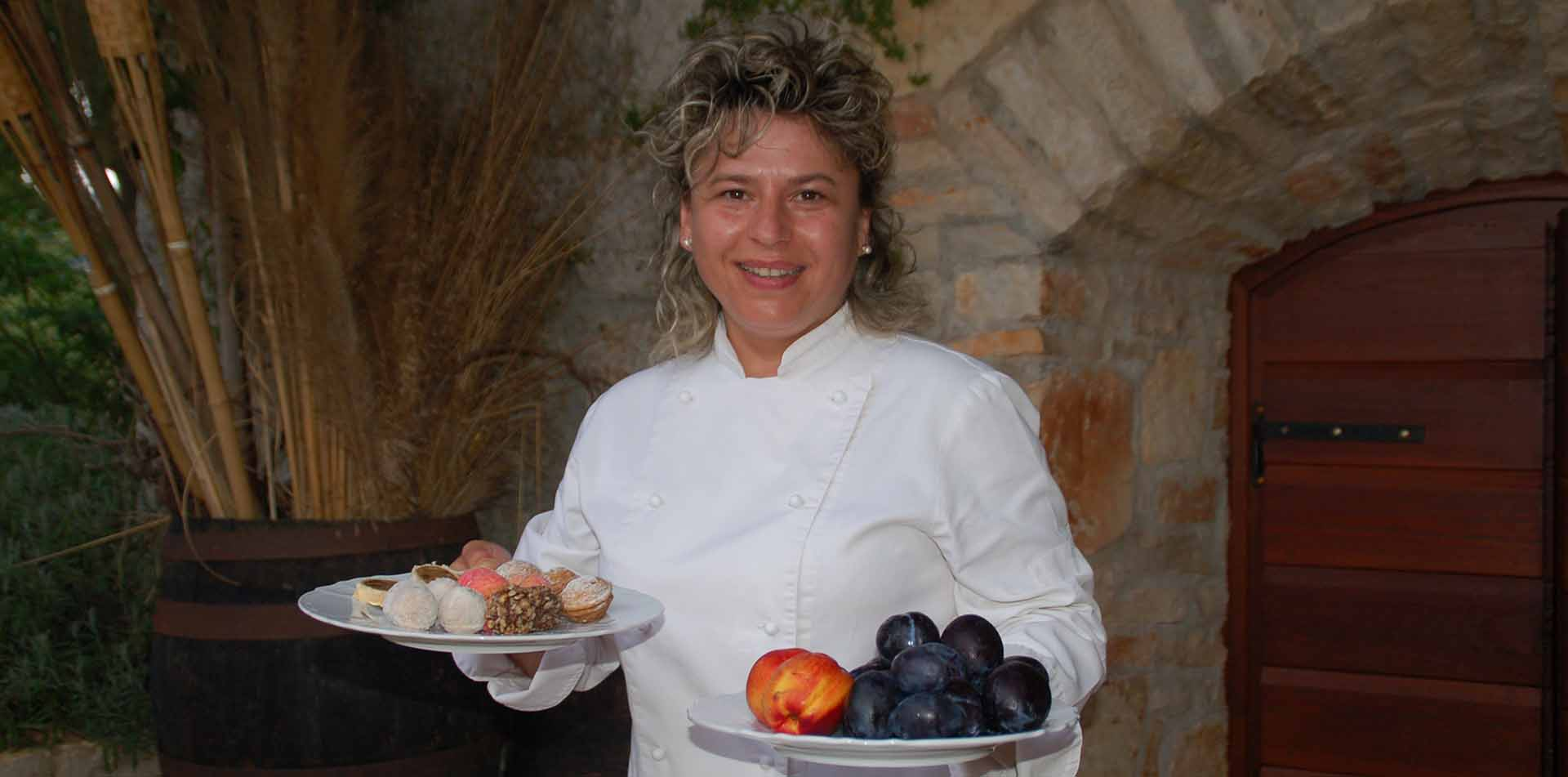 Europe Croatia Istria happy female chef carrying plates of fruit and pastries - luxury vacation destinations