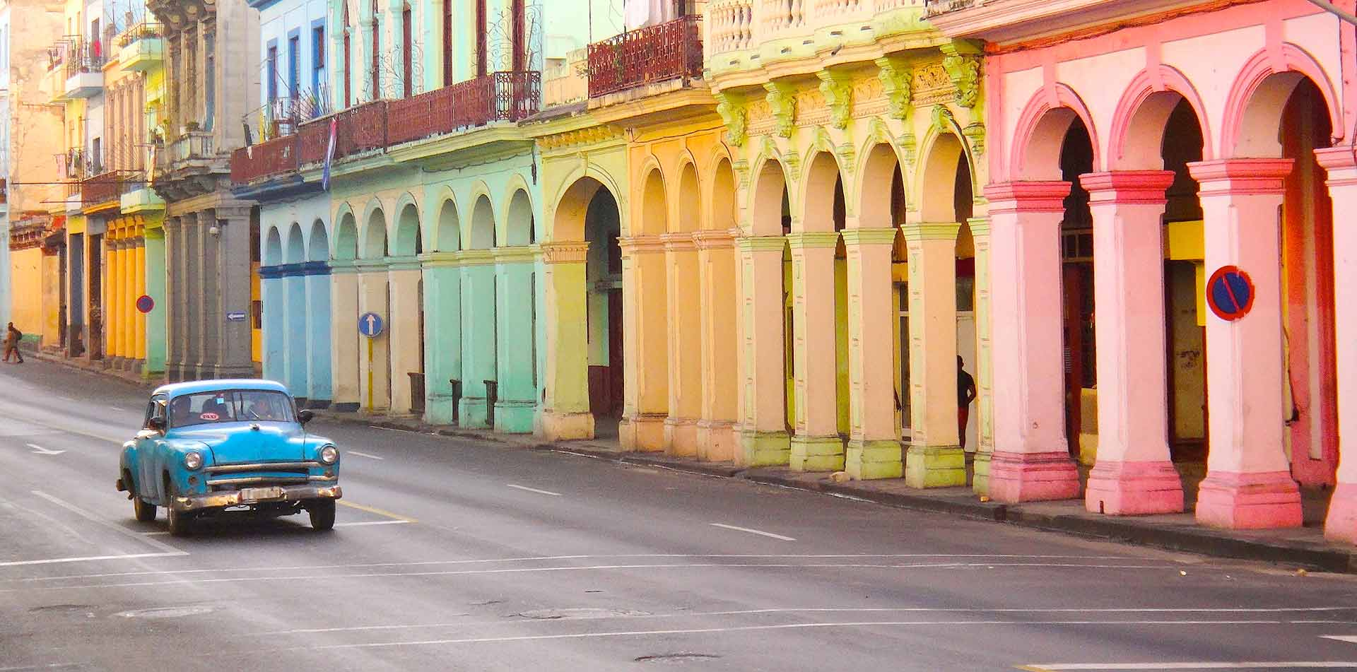 North America Caribbean Cuba Havana local street pastel color buildings classic car - luxury vacation destinations