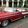 North America Caribbean Cuba Havana old street red classic convertible car smile happy pose - luxury vacation destinations