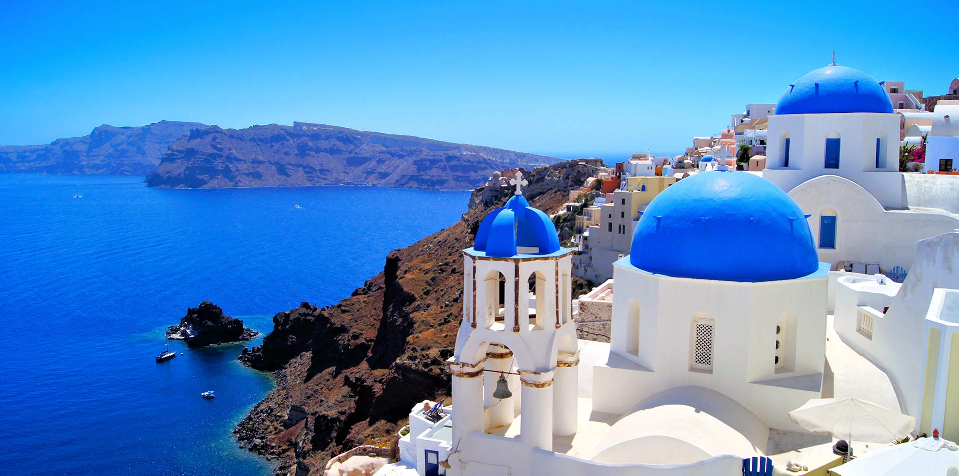 Europe Greece Santorini blue and white buildings on cliffside overlooking ocean - luxury vacation destinations