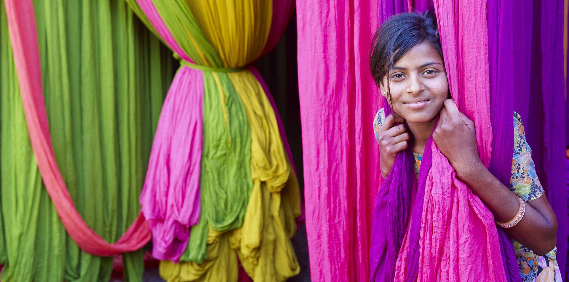 Asia India local girl peeking through colorful fabric at sari factory - luxury vacation destinations