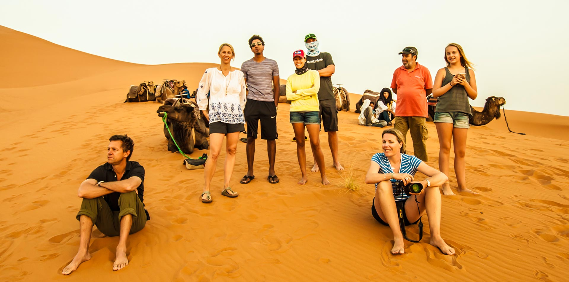 Africa Morocco Sahara Desert happy group posing in tan sand dunes camels resting - luxury vacation destinations