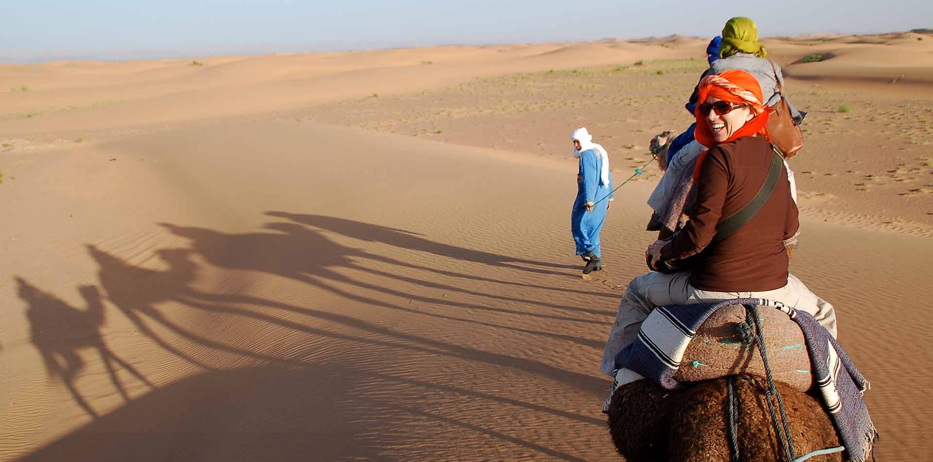 Classic Journeys Founder Susan Piegza on Camel in Sand Dunes of Morocco