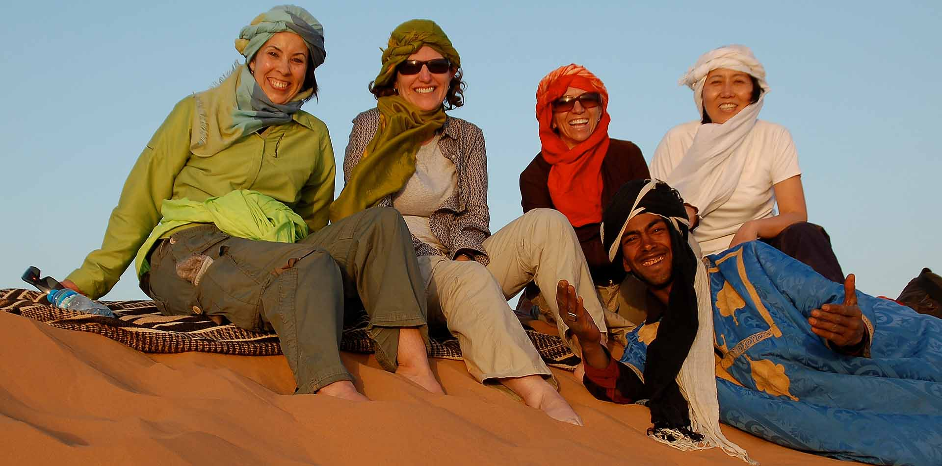 Classic Journeys Guide Saida with Travelers on Sand Dune in Morocco