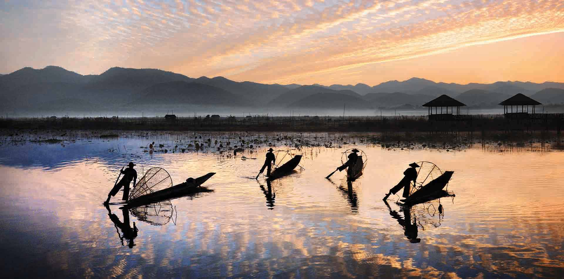 Asia Myanmar traditional Burmese fishermen on boats tranquil lake at sunset scenic mountains - luxury vacation destinations