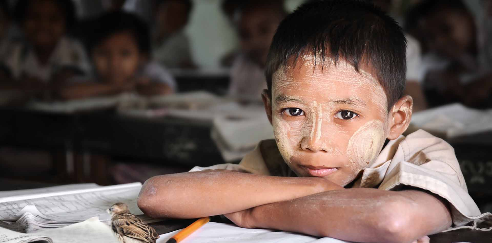 Asia Myanmar young local schoolboy with face painting sitting at classroom desk - luxury vacation destinations