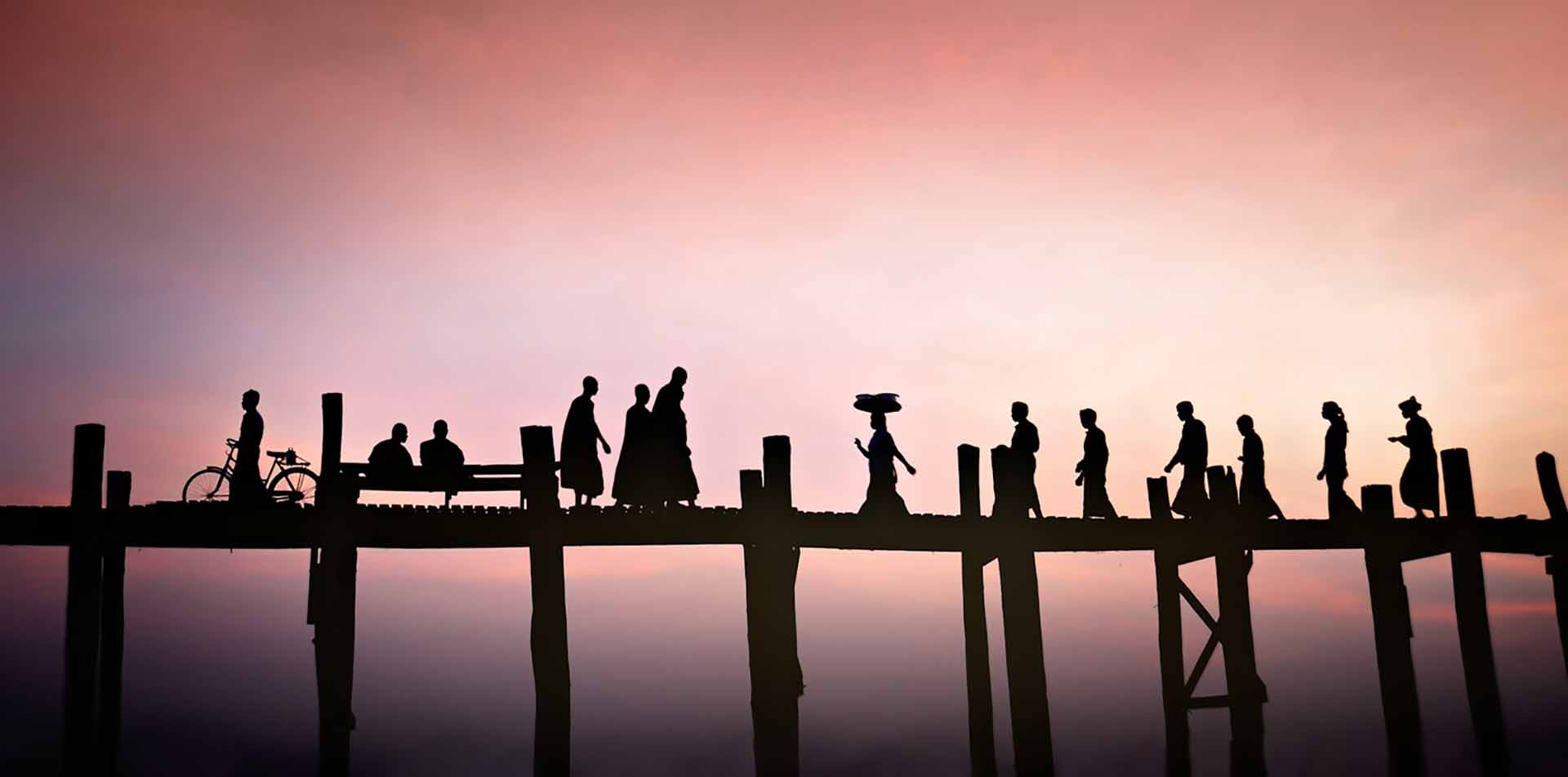 Asia Myanmar U Bein Bridge beautiful colorful sunset dark silhouettes of pedestrians crossing - luxury vacation destinations