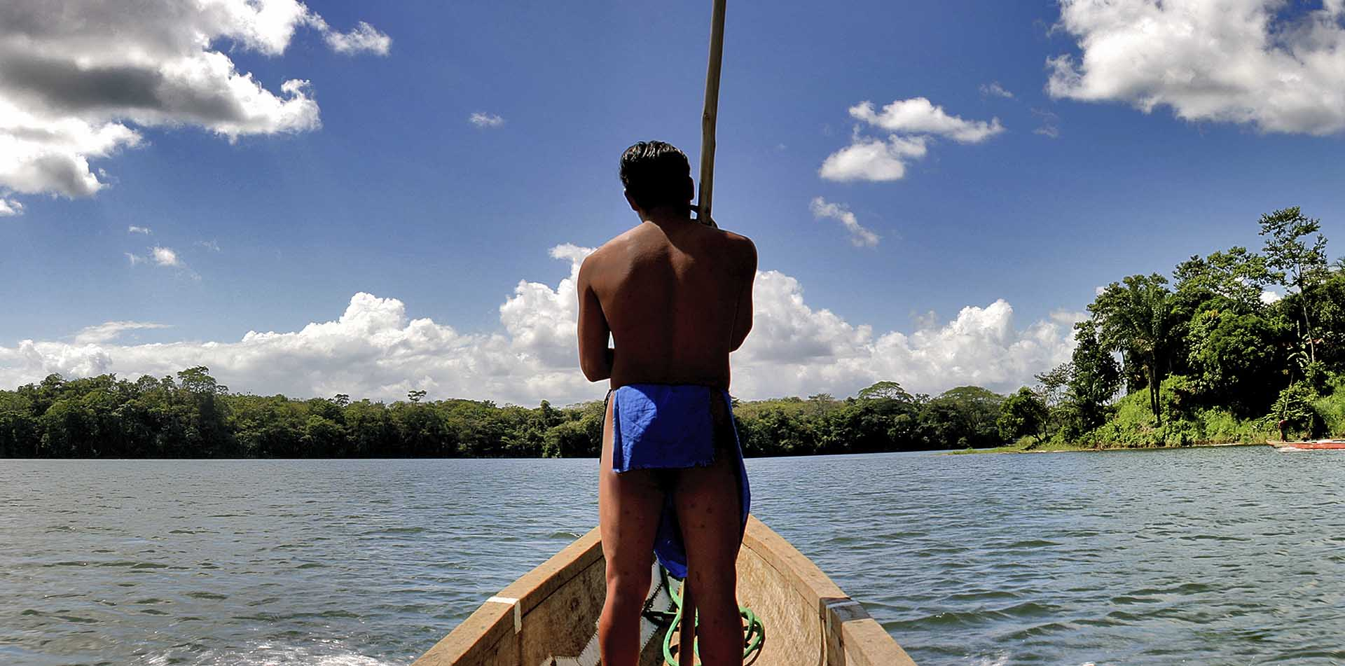 Central America Panama local Embera man in a wooden boat - luxury vacation destinations