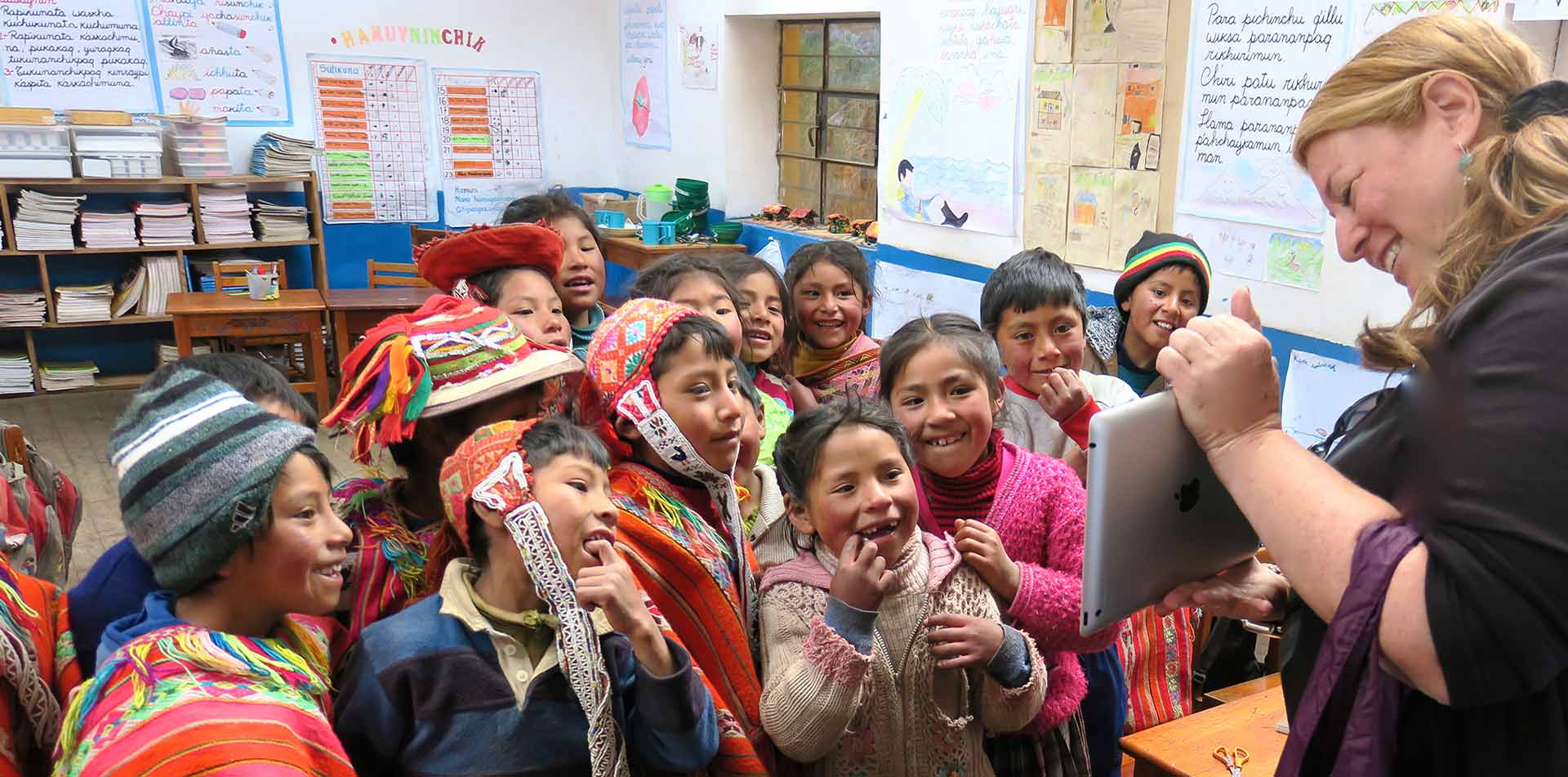 South America Peru Quechua schoolchildren in traditional bright attire smiling looking at iPad - luxury vacation destinations