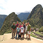 South America Peru family smiling posing in front of scenic Machu Picchu ancient Inca ruins - luxury vacation destinations