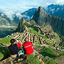 South America Peru couple taking photos of scenic Machu Picchu and ancient Inca ruins - luxury vacation destinations