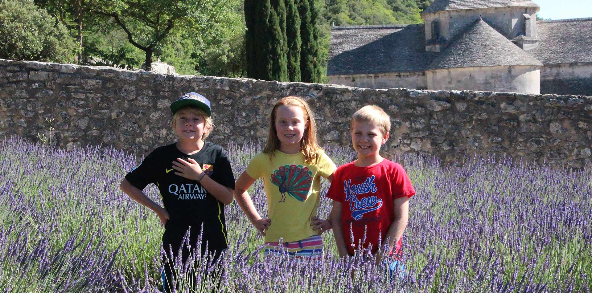 Europe France Provence children smiling in lavender fields in Luberon Regional Nature Park - luxury vacation destinations