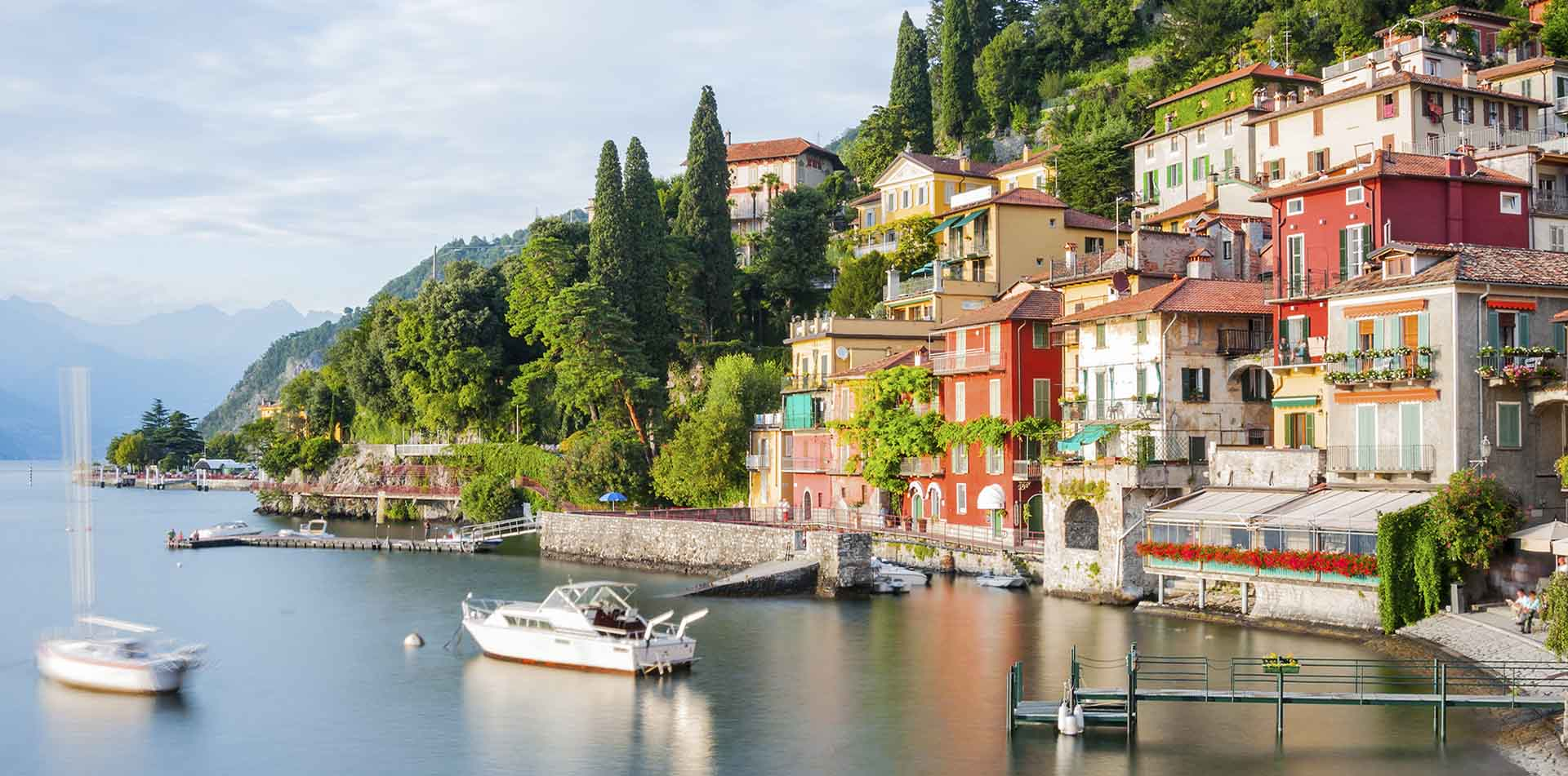 Europe Italy Lake Como Menaggio scenic town historic colorful houses on green hill boat dock - luxury vacation destinations