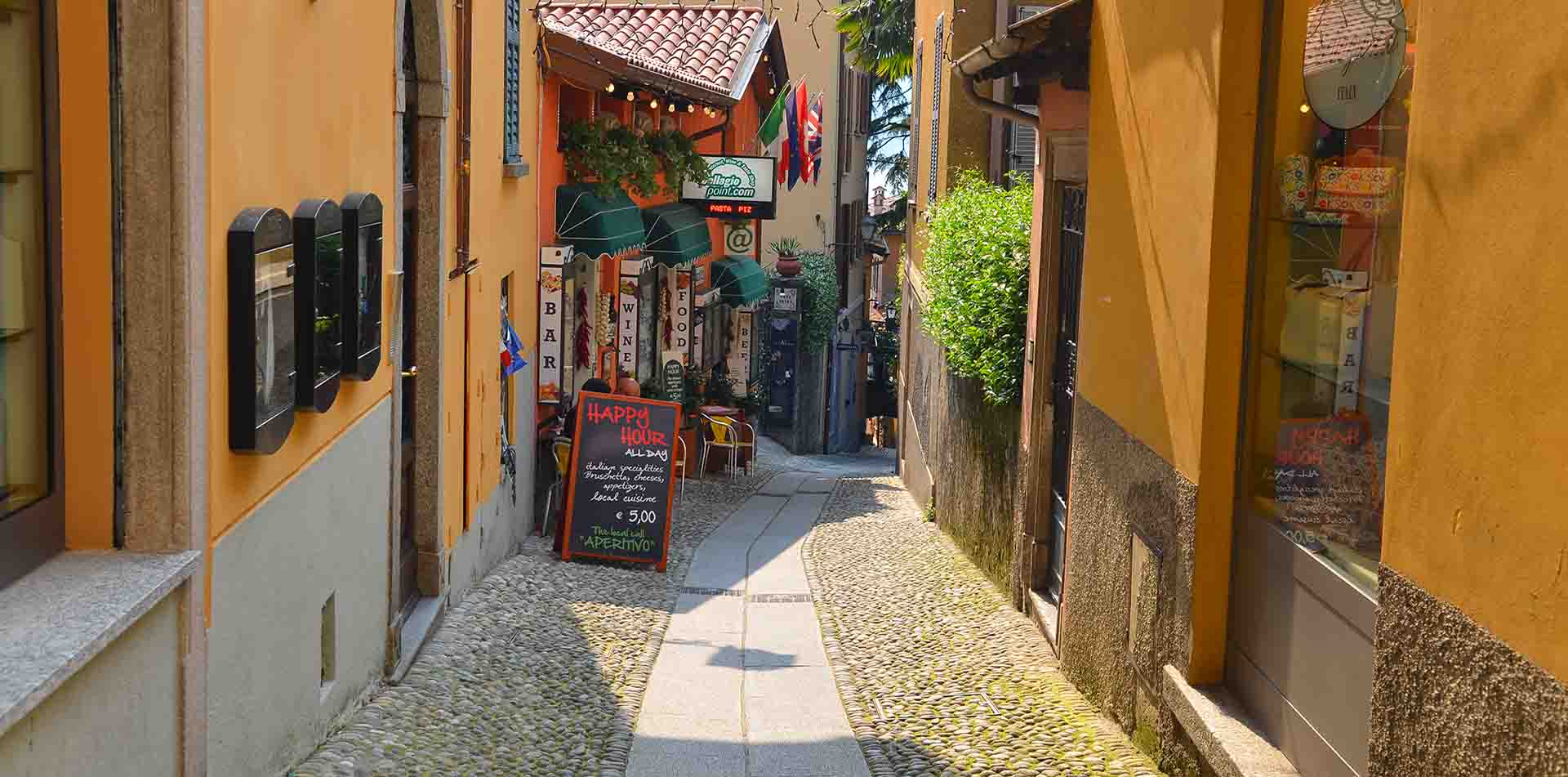 Europe Italy Lake Como Bellagio colorful buildings happy hour sign narrow cobblestone street - luxury vacation destinations