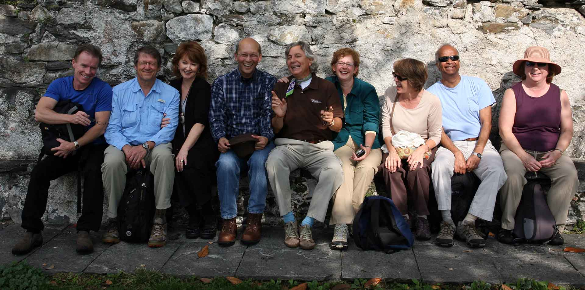 Europe Italy Italian Lakes happy group sitting against rock wall smiling laughing - luxury vacation destinations