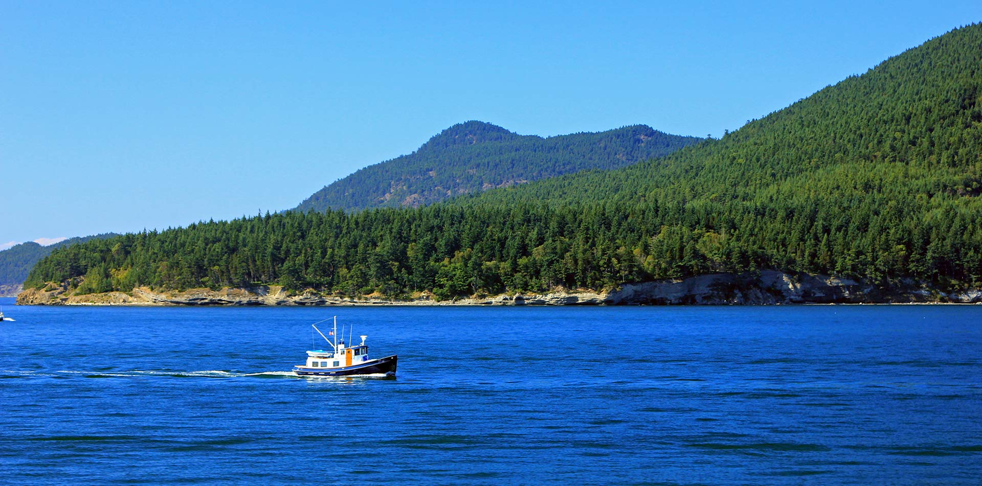 US Pacific Northwest Puget Sound San Juan Island fishing boat mountain forest coastline - luxury vacation destinations