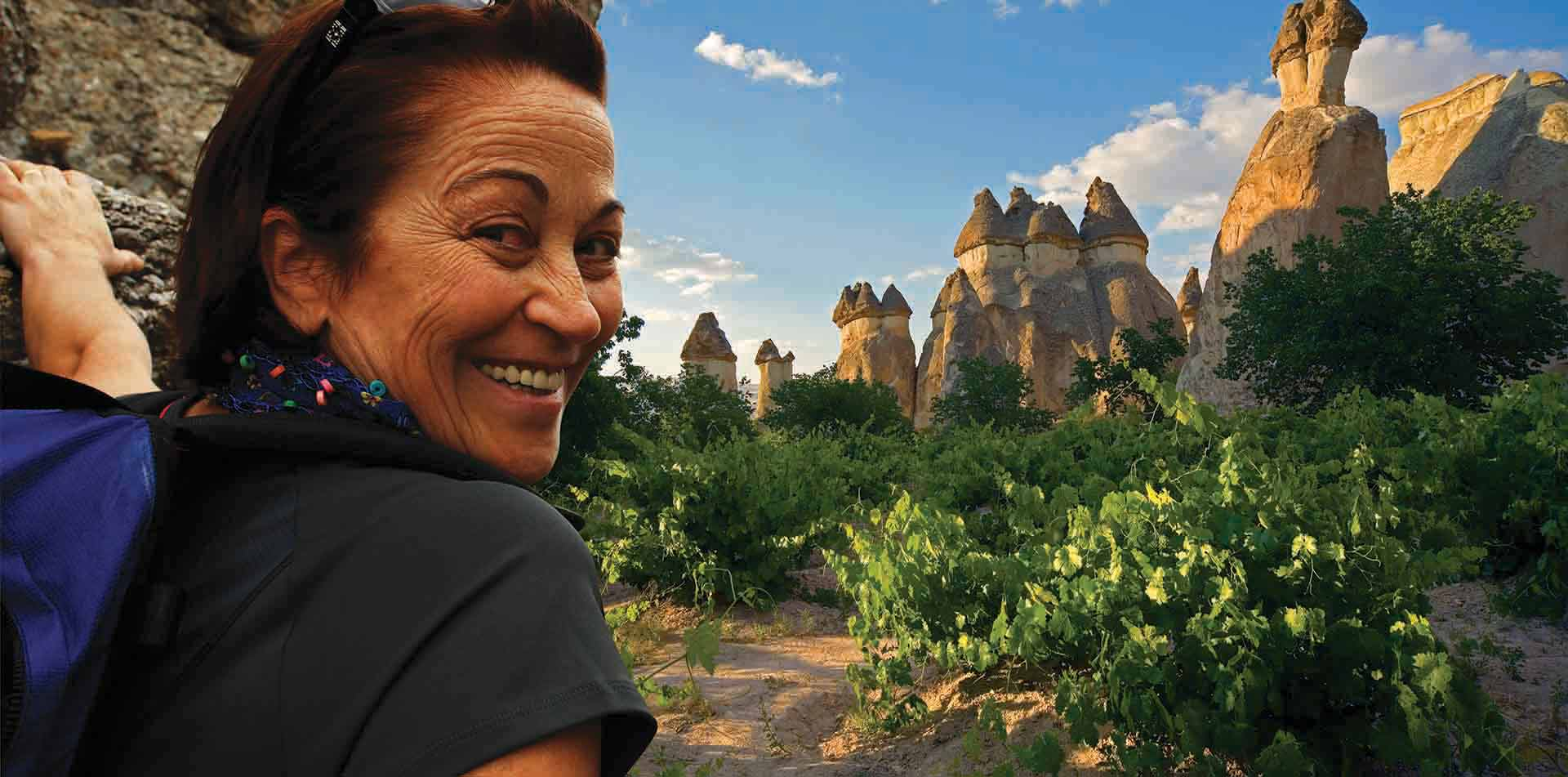 Turkey woman at Goreme National Park and Rock Sites of Cappadocia stone spires and chimneys - luxury vacation destinations