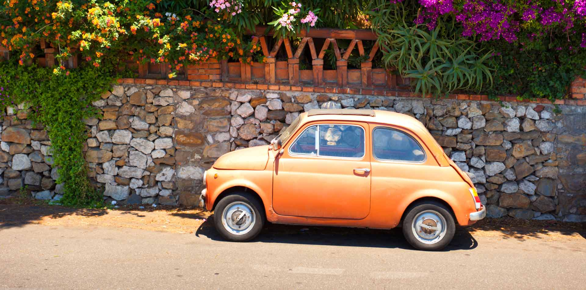 Europe Italy small orange Italian car on the side of a local plant-lined street - luxury vacation destinations