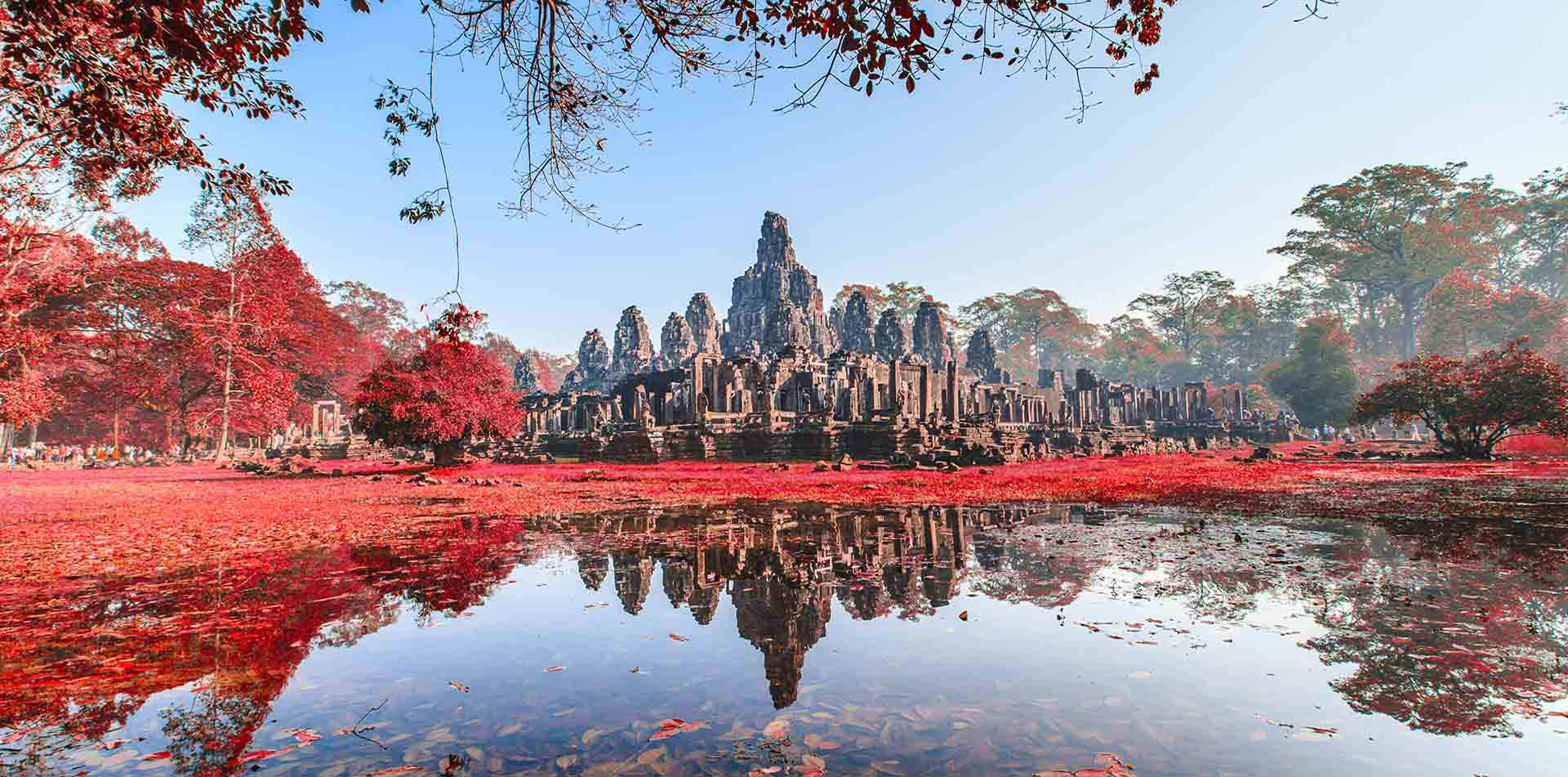 Asia Cambodia Siem Reap Angkor Wat Bayon temple surrounded by red trees - luxury vacation destinations