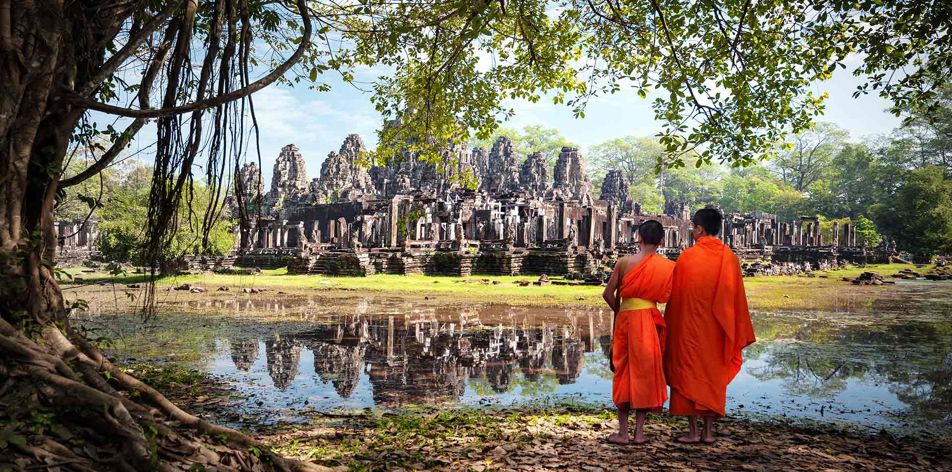 Asia Cambodia Siem Reap boy monks in Angkor Wat overlooking Bayon temple - luxury vacation destinations
