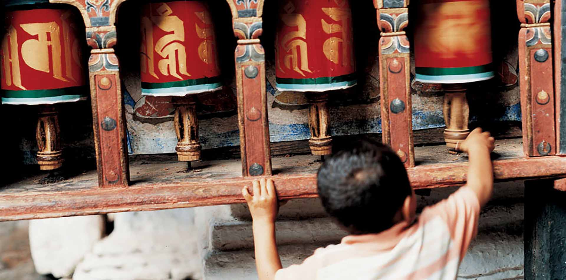 Asia Bhutan child spinning Buddhist prayer wheels in Himalayan mountains - luxury vacation destinations