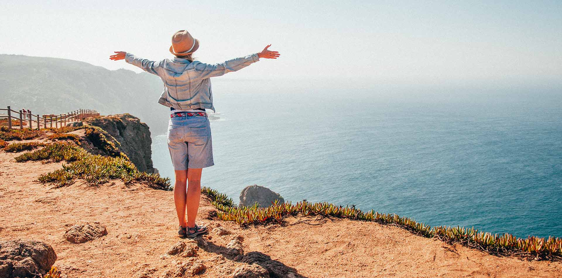 Portugal Sintra Mountain Range woman with open arms overlooking Cabo da Roca Cape Roca - luxury vacation destinations