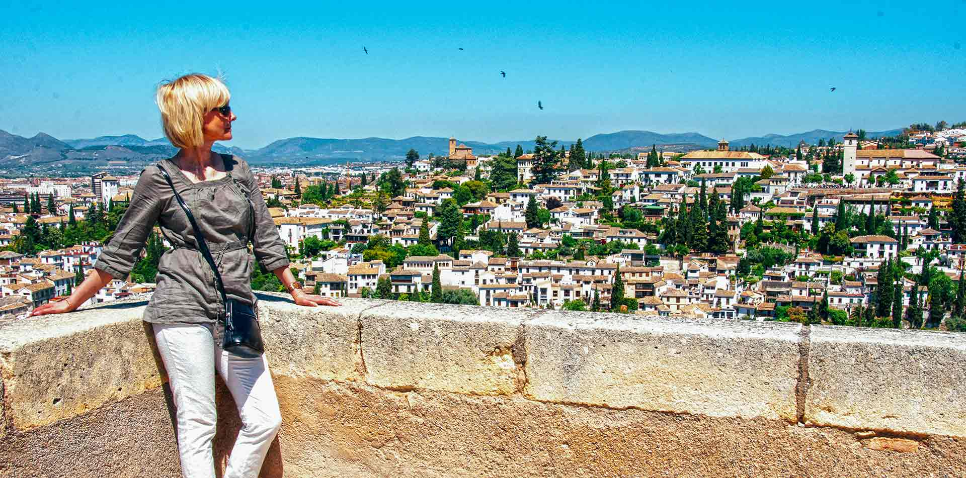 Europe Spain Andalucia woman posing on the walls of the Alhambra in Granada - luxury vacation destinations